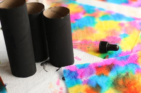 Colourful paper towel beside black-painted paper towel rolls