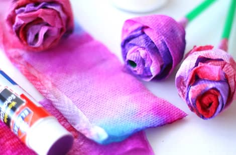 Completed paper towel roses beside paper towel strips still to be rolled