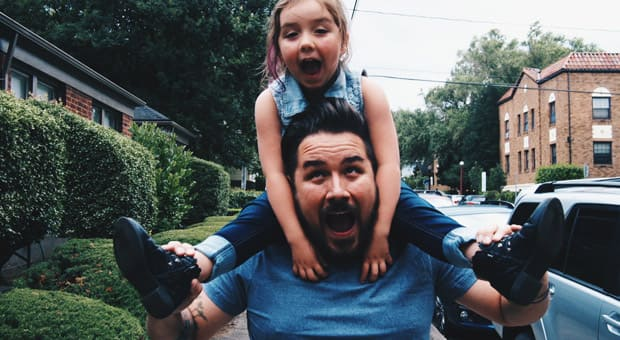 A daughter riding on her father's shoulders and both are making silly faces