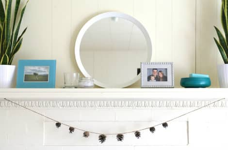 A fireplace mantel with framed photos, plants and a mirror, with the completed pine cone garland hanging below