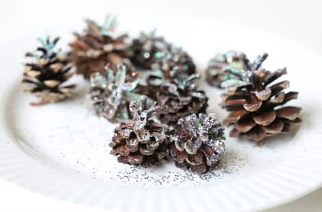 A pile of freshly glittered pine cones sitting and drying on a white plate