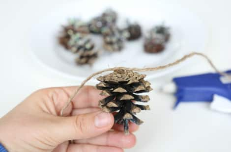 Holding a pine cone up to twine to glue one, with glittered pine cones on plate and glue gun in background