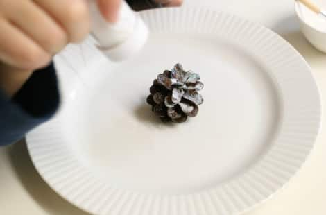 A child sprinkling glitter onto a pine cone over top of a white plate