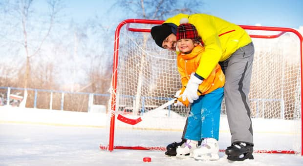 A father playing hockey with his son