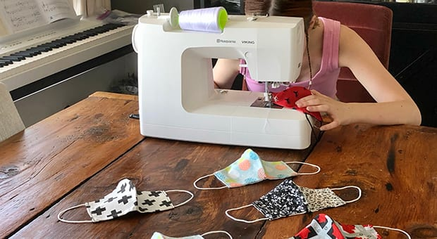 Tween site behind sewing machine as homemade masks are strewn on the table