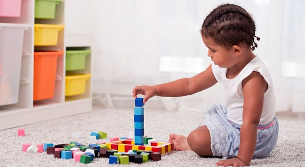 Little girl sitting on the floor of her bedroom, playing with blocks