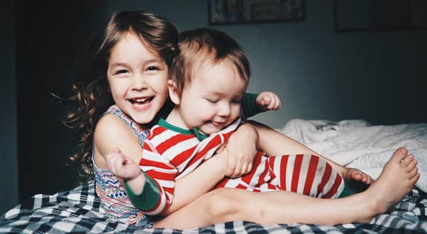 Sister and brother laughing on a bed