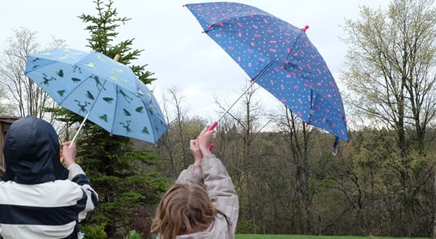 Two kids holding umbrellas in the rain.