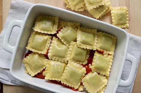 Ravioli placed on tomato sauce in a casserole dish.