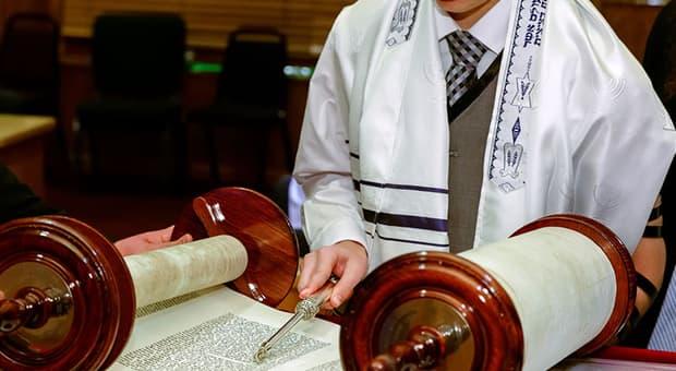 Jewish man reads the Torah for bar mitzvah.