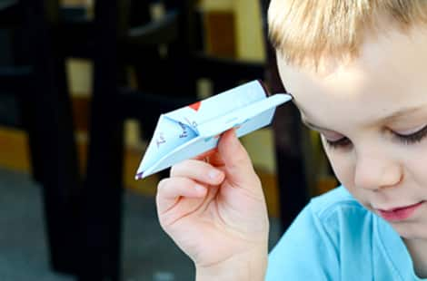 A child holding an airplane made of a Valentine's card