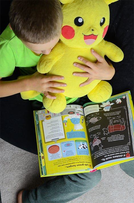 Little boy quietly reads a book and holds a stuffed Piccachu.
