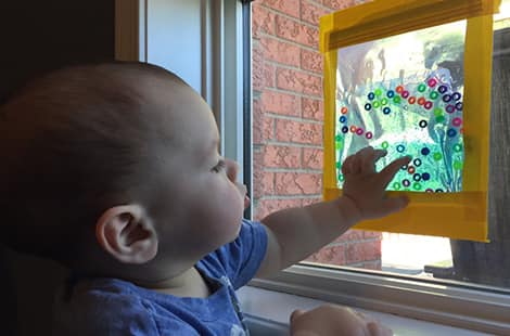 Baby reaching for a sensory bag taped to a window.