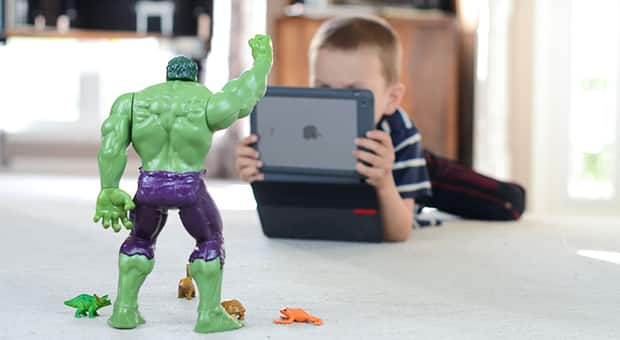 Kid holding iPad to film toys.