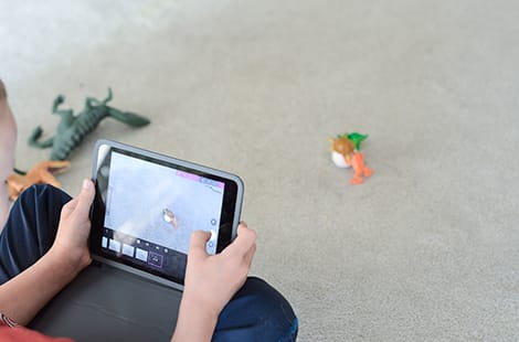 Child holds iPad to film their toys.