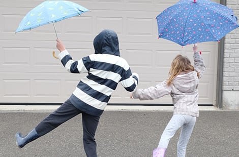 Two kids dance with umbrellas in the air.