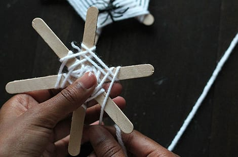 The white yarn is weaved above and below the popsicle sticks, resembling a spider's web.