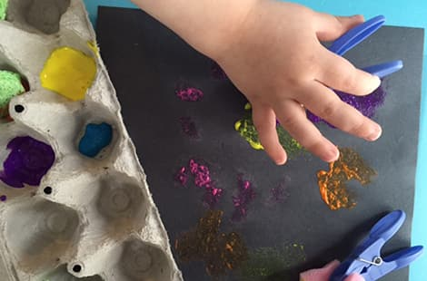 Child painting with sponge-brushes made out of clothes pins.