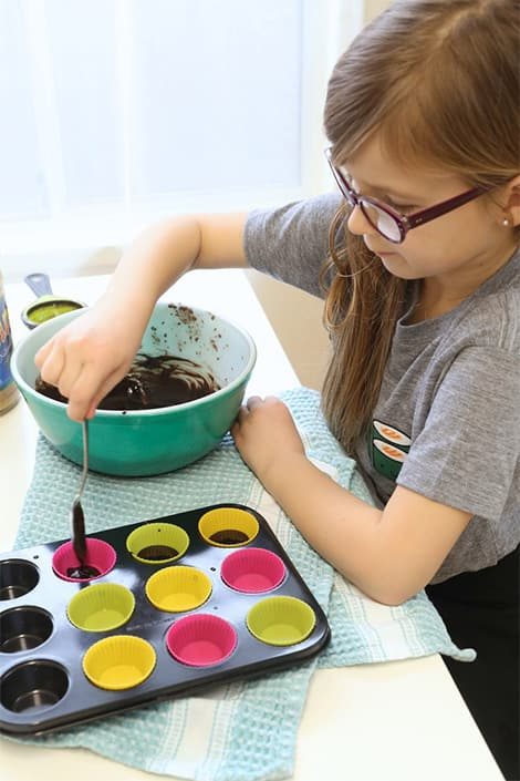 Little girl spoons chocolate into silicon cups.