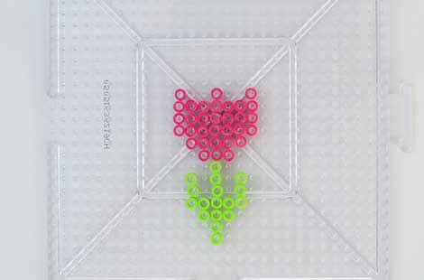 A pink perler bead tulip on a pegboard.