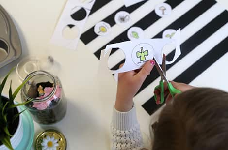 Little girl cuts out coloured in pictures from scavenger hunt .pdf
