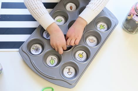 Child secures each illustration in the muffin tin.