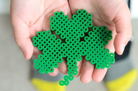 Child holding shamrock made of perler beads.