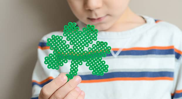 Little boy holds up perler bead shamrock.