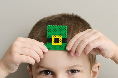 A little boy holds a leprechaun hat made of perler beads to his forehead.