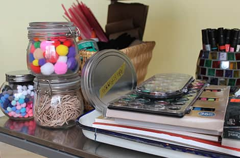 Paints and pom-poms and elastic bands on the STEAM shelf.