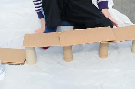 Cardboard bridge built using cardboard and toilet paper rolls.