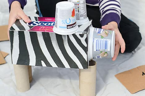 An animal made out of recyclables like tissue boxes, yogurt containers and paper towels.