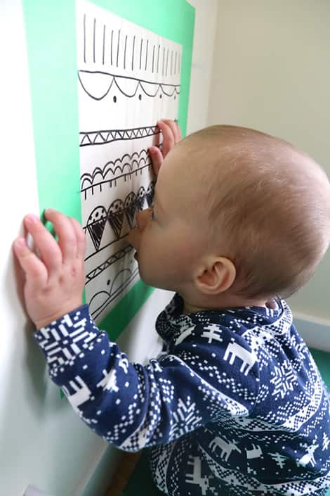 Baby gets lip stuck on sticky wall contact paper.