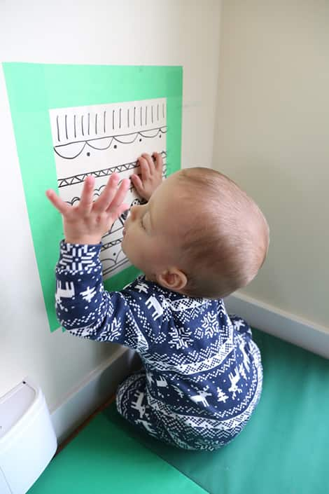 Baby pulls hand away from sticky wall.