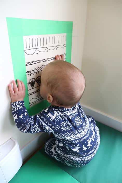 Baby sticks head against contact paper.