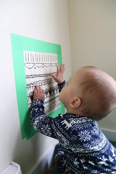Baby interacting with wall.