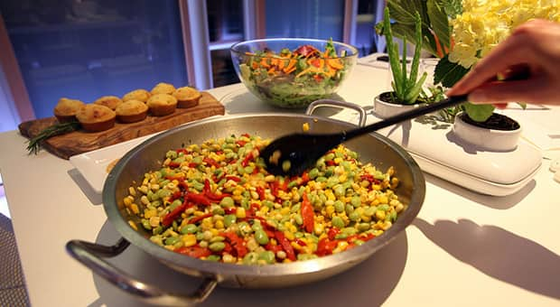 A bean salad is being stirred, baked rolls