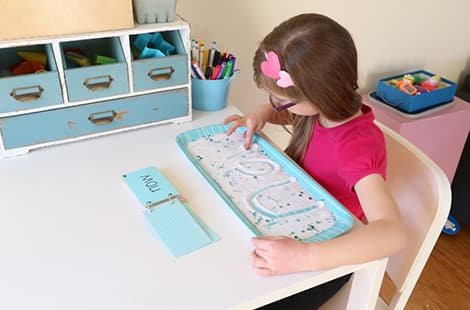 Little girl spelling out the word