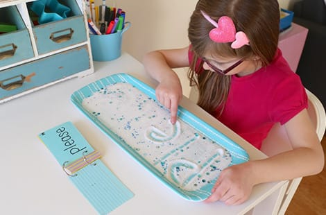 Little girl spells a word in the salt tray.