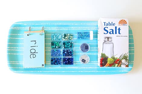 Blue tray full of supplies that include salt, sequins and spelling book.