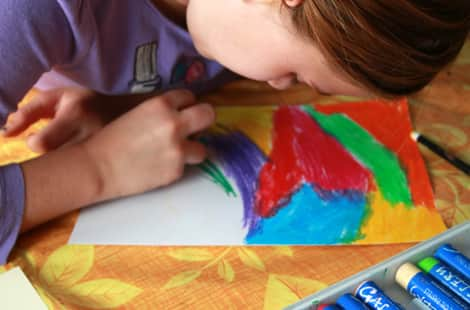 A young girl colouring a piece of paper in rainbow shades