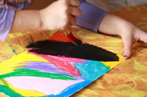 A young girl covering the coloured paper in black paint