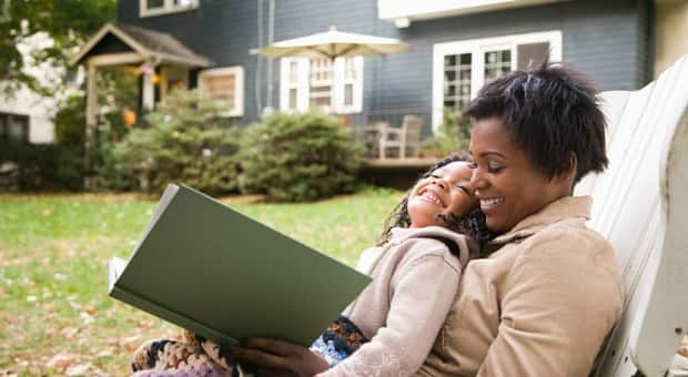 A woman reading with her daughter outside