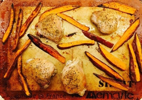 A baking tray with chicken thighs and sweet potatoes