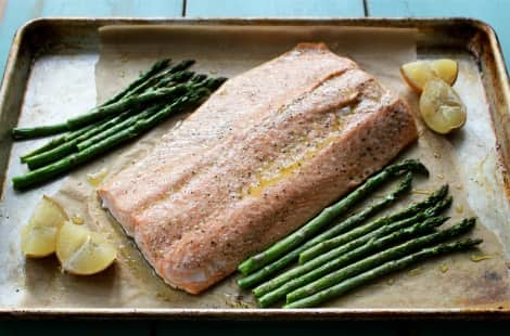 A baking sheet with salmon, asparagus and lemon