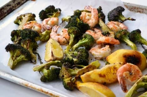 A baking tray with broccoli, shrimp and lemon