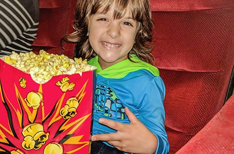 Child holding popcorn is excited to watch movie at theatre.