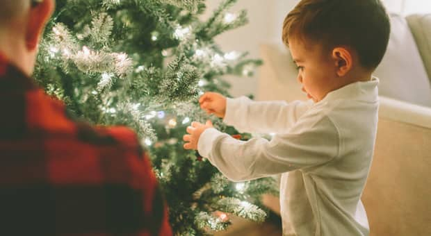 A little boy with his parent decorating a Christmas tree