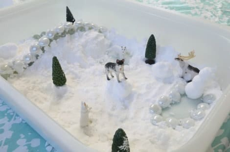 An arctic scene with wolves, trees and a snowman created inside the tray of snow dough