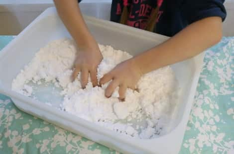 A child moulding the snow dough in its tray